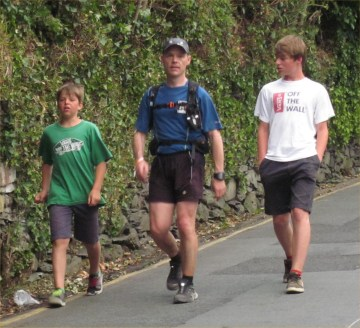 Tom entering Ambleside flanked by his sons.