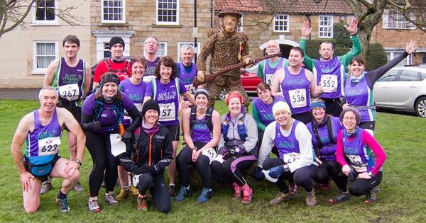 Elvet Striders pose for a photo with Great Ayton's WWI commemorative sculpture