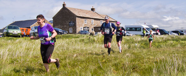 Diane, Dave and Mel pass the Tan Hill Inn, the highest point of the DT30 trail race